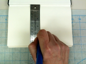 Measure book length, then using a ruler and X-Acto knife, cut the pages in half from the spine outward